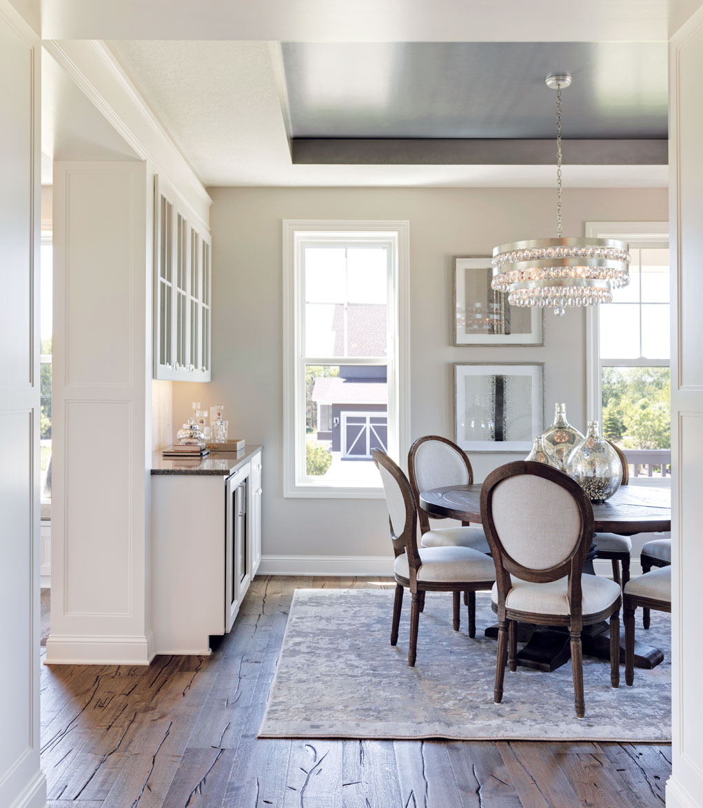 A dining room with a metallic ceiling, rustic floors, and elegant table, chairs and chandelier.
