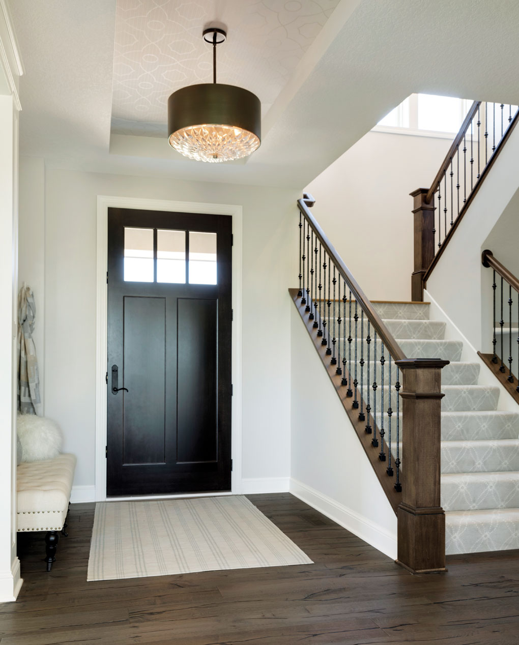 An entry opens up to a staircase leading to an upper level and elegant light hanging overhead.