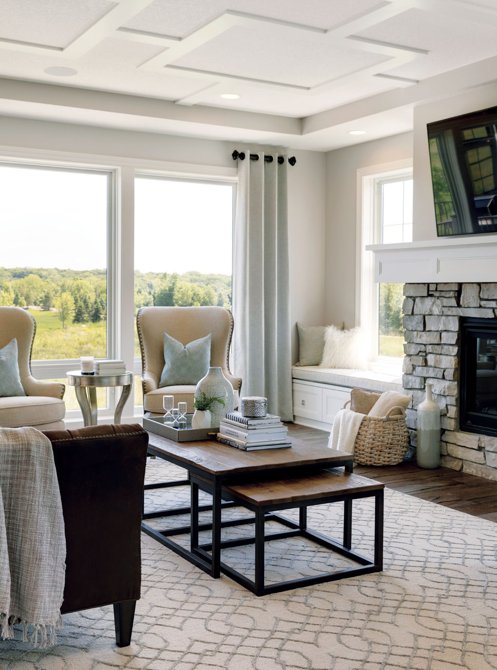 A great room with a coffered ceiling, floor to ceiling windows, and stone fireplace is a comfortable, welcoming space.