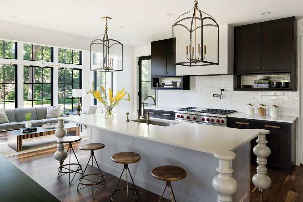 The open kitchen blends modern and traditional with a white subway tile backsplash, ebony-stained walnut cabinets, quartz-topped island, and stylized turned-wood legs.