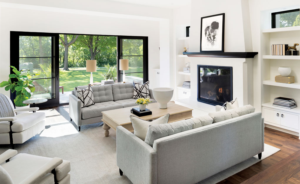 A living room accented with a coffee tables, couches and chairs, and a fireplace.