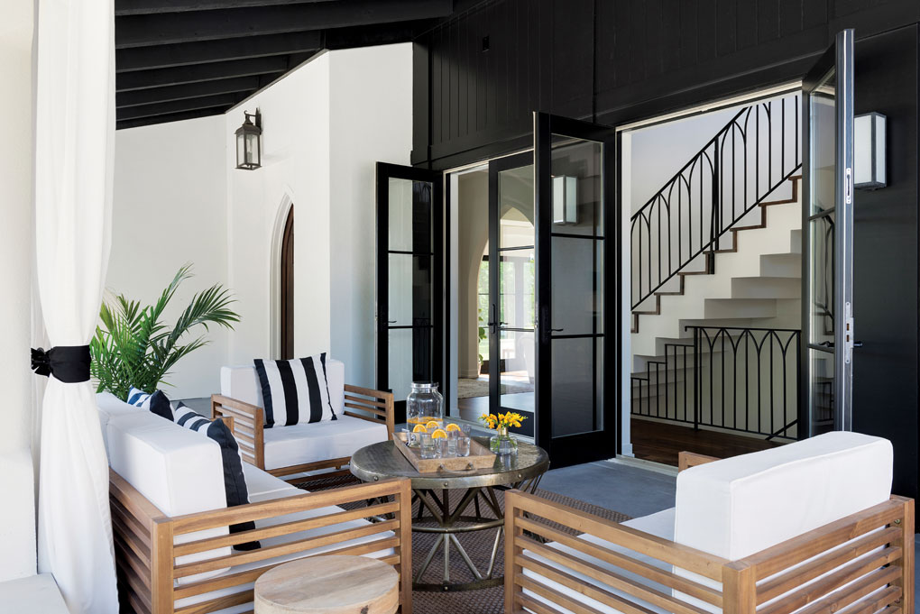 The inviting loggia (covered patio) is lined with French doors that display the arch detail of the wrought-iron staircase, which echoes the arch of the front door.