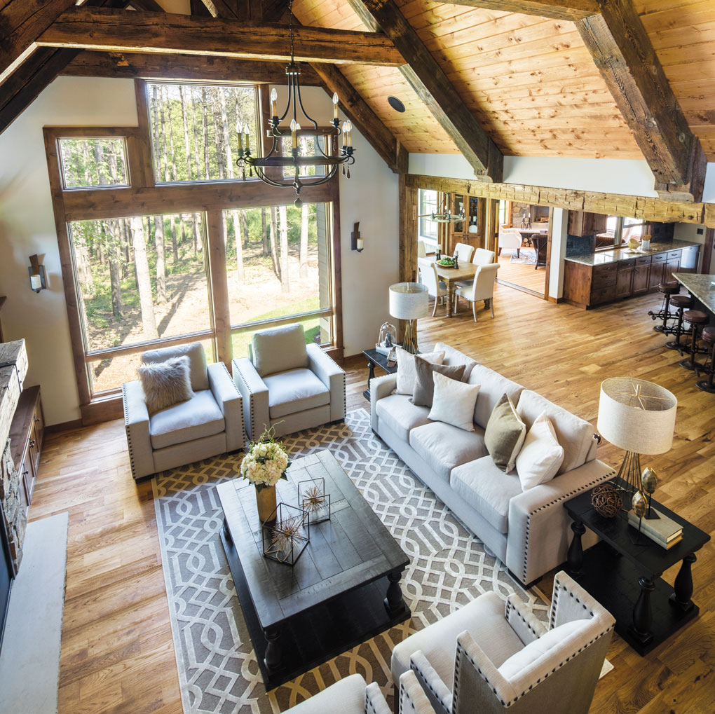 An overhead view of a great room with a floor-to-ceiling stone fireplace, coffee table surrounded by chairs and a couch, large windows and a vaulted ceiling.