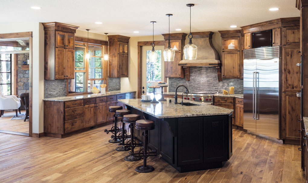 The black, hand-rubbed finish of the island lends contrast to the warm alder of the other cabinetry in the open kitchen.