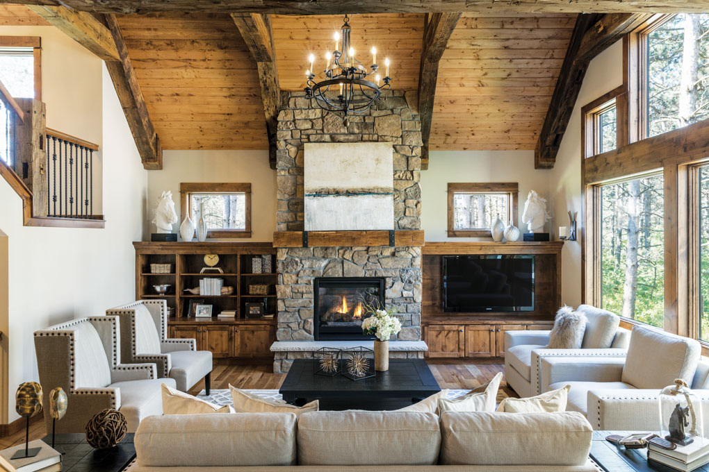 The great room's floor-to-ceiling stone fireplace has a reclaimed timber mantel adorned by iron strapping and studs.