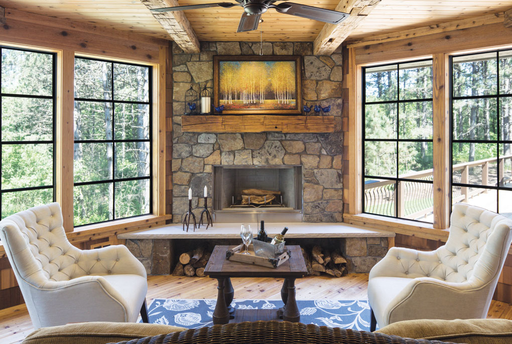 Chairs and a stone fireplace inside a 3.5 season porch.