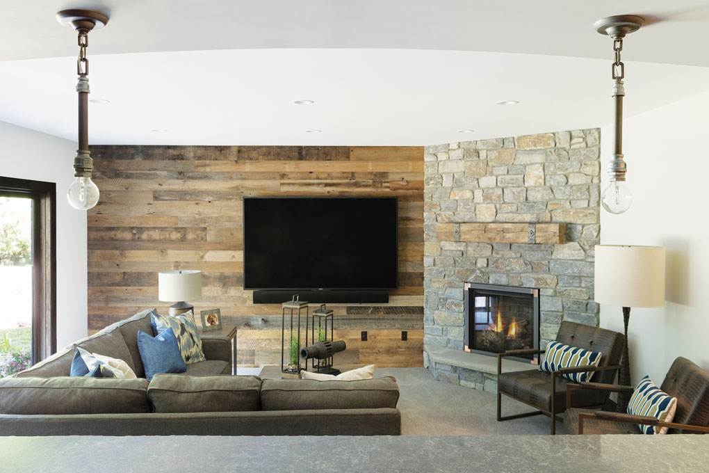 A basement features a TV mounted on the far wall that is made out of wood. In front of it is a sectional sofa facing a fireplace, and oversized Edison bulbs hang overhead.