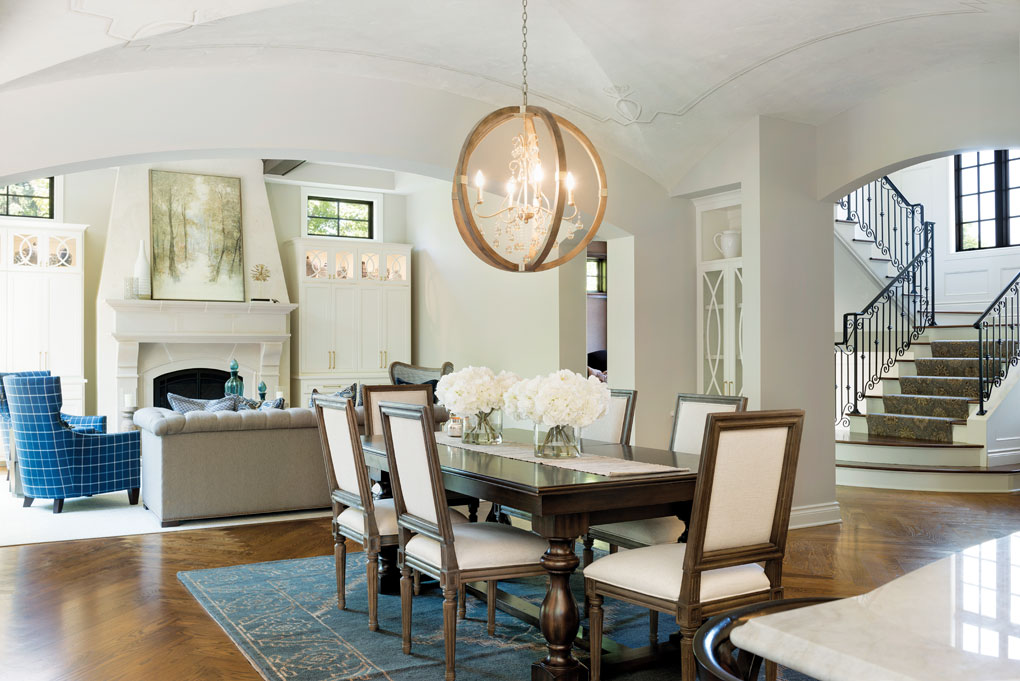 A dining room features an elegant set of table and chairs with a chandelier hanging overhead. It flows seamlessly into the living room, kitchen and stairway leading to an upper level.
