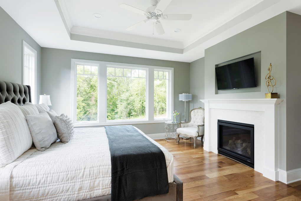 A master bedroom complete with fireplace and a TV mounted on the wall above it.