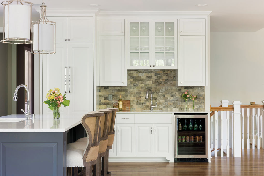 A nook off to the side of a kitchen features a counter with brick backsplash, and a small sink and fridge.