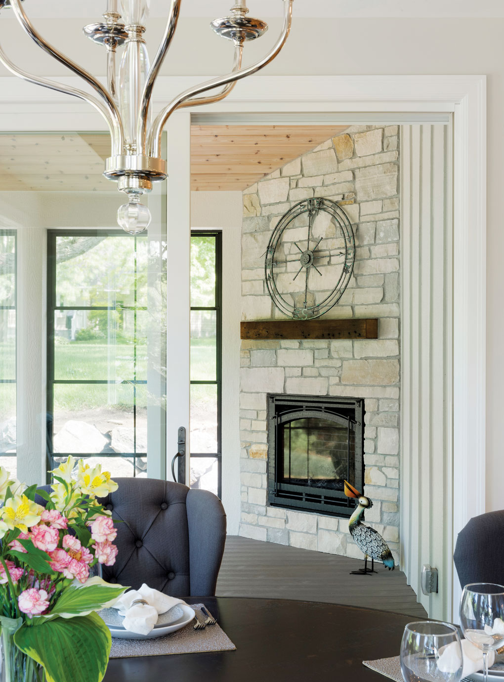 A look into a patio reveals a floor-to-ceiling, stone fireplace with a large clock set on the mantel.