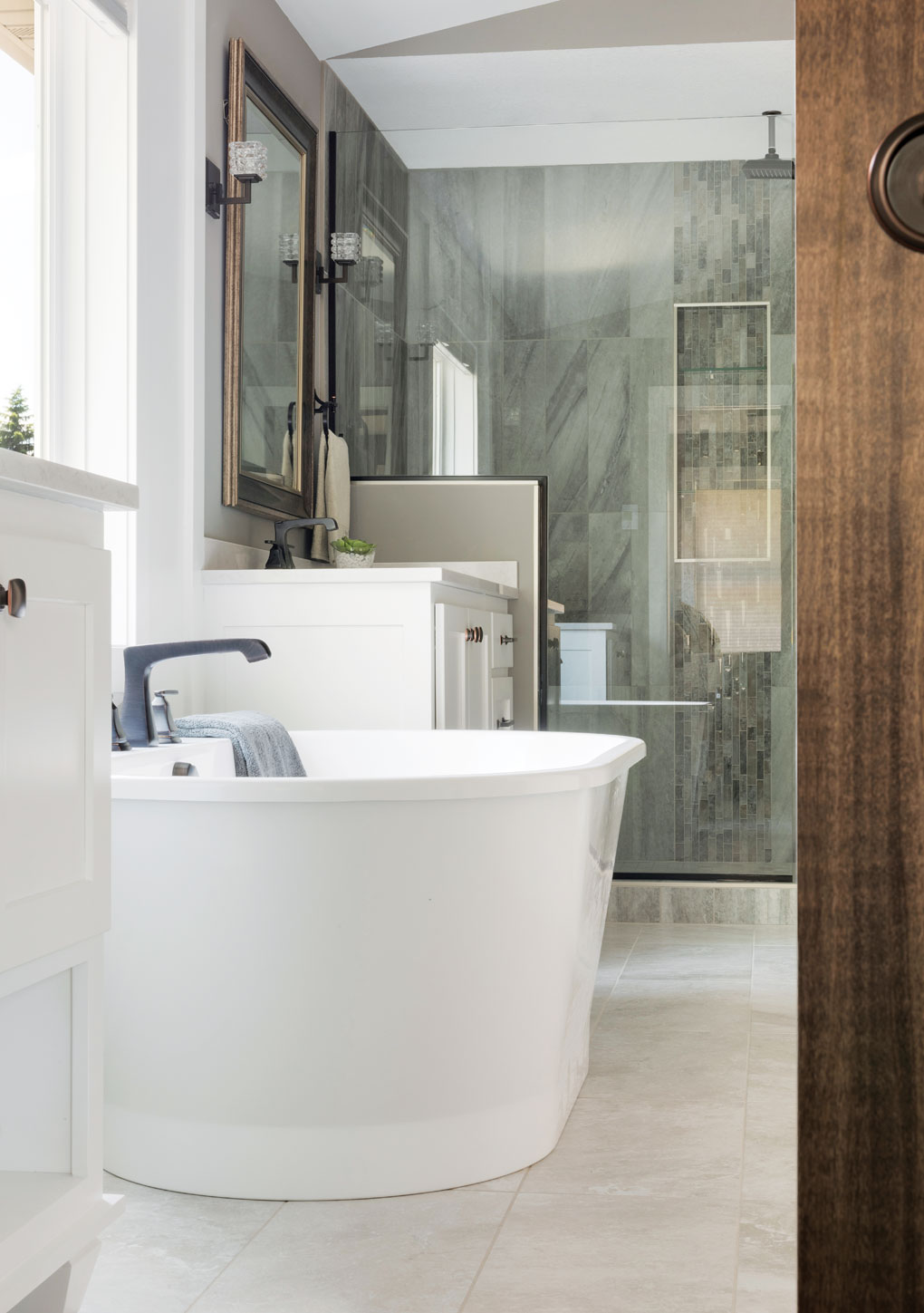 A master bath featuring a soaking tub, rain shower, decorative tile work and a vaulted ceiling.