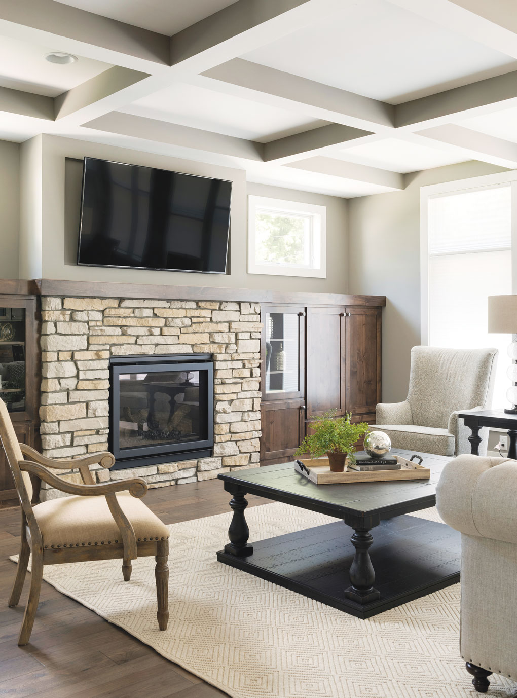 A living room with a coffered ceiling, television set above a fireplace, and a coffee table surrounded by a sofa and chairs.