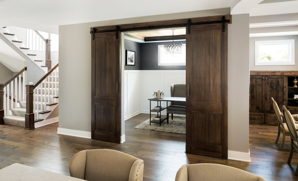 Sliding doors reveal an office in the lower level of a home.