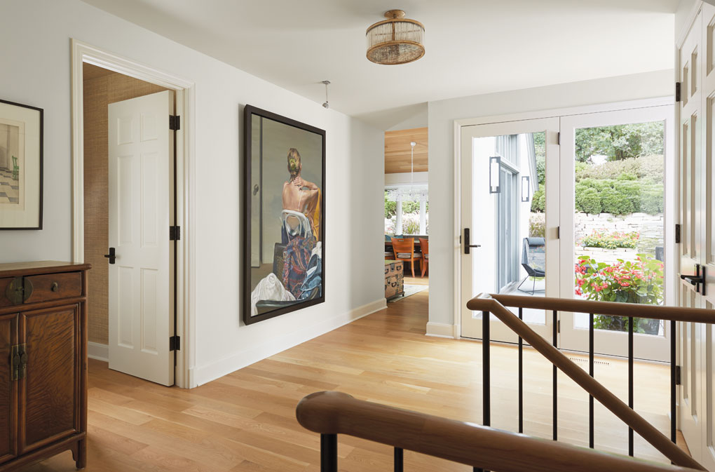 A painting hangs on the wall in a landing area of a home.