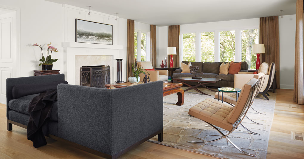 A living room furnished with a fireplace, Barcelona chairs, sofa and large windows that look out to the site's natural surroundings.