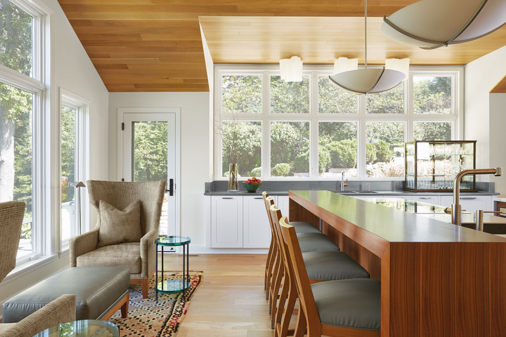 A kitchen nook that provides a seating area and windows looking out to the site's natural surroundings is set next to a bar.