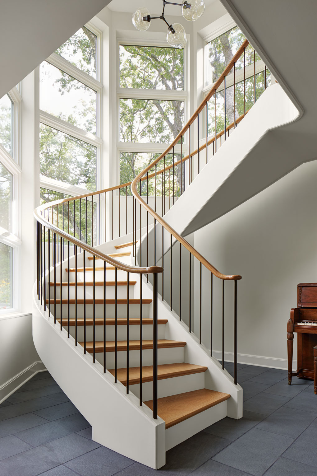 A sculptural staircase attached only at the top and bottom is surrounded by windows.