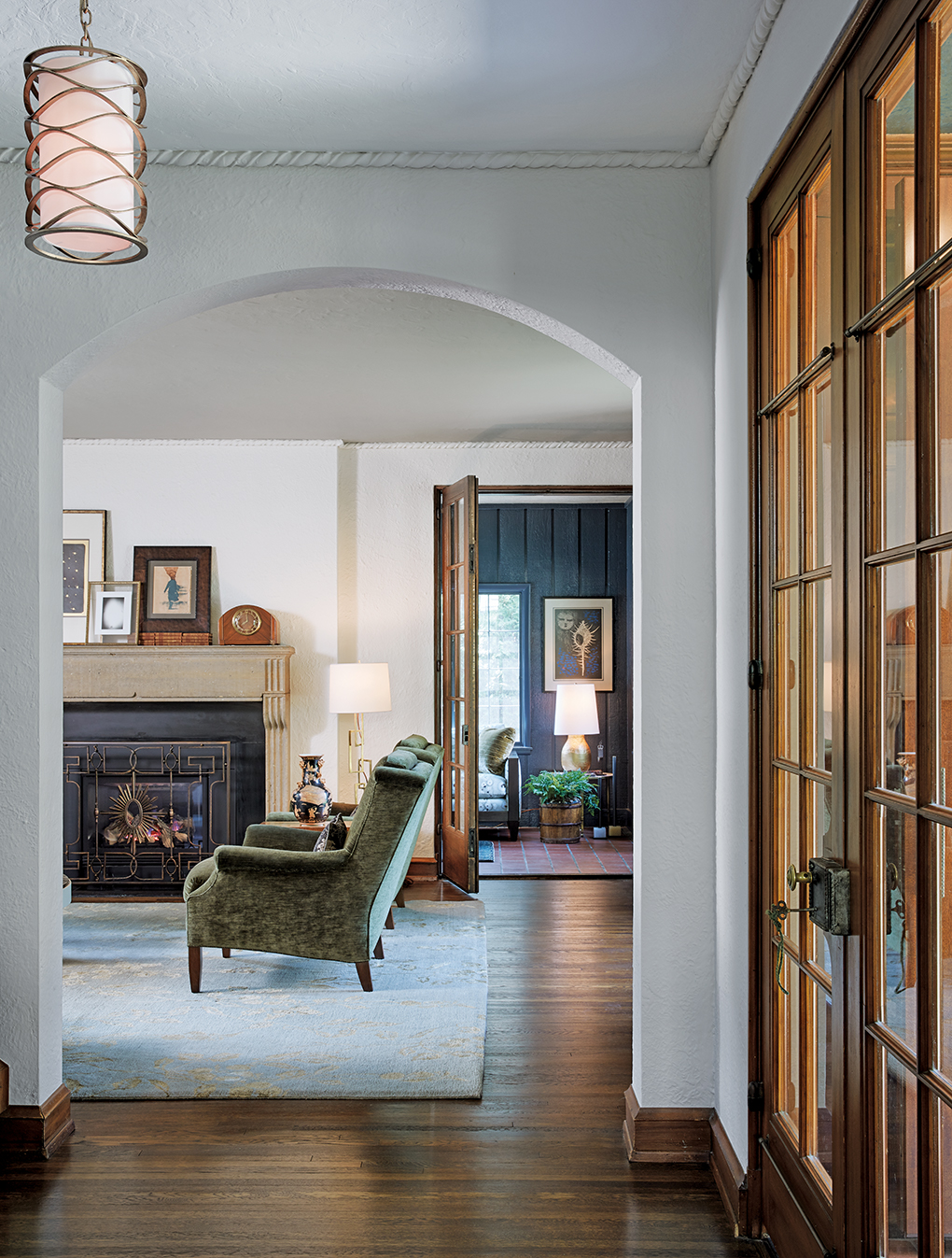 A graceful archway opens from the foyer to the living room, showing a two chairs on a rug set next to a fireplace along with a glimpse of the deep navy sunroom.