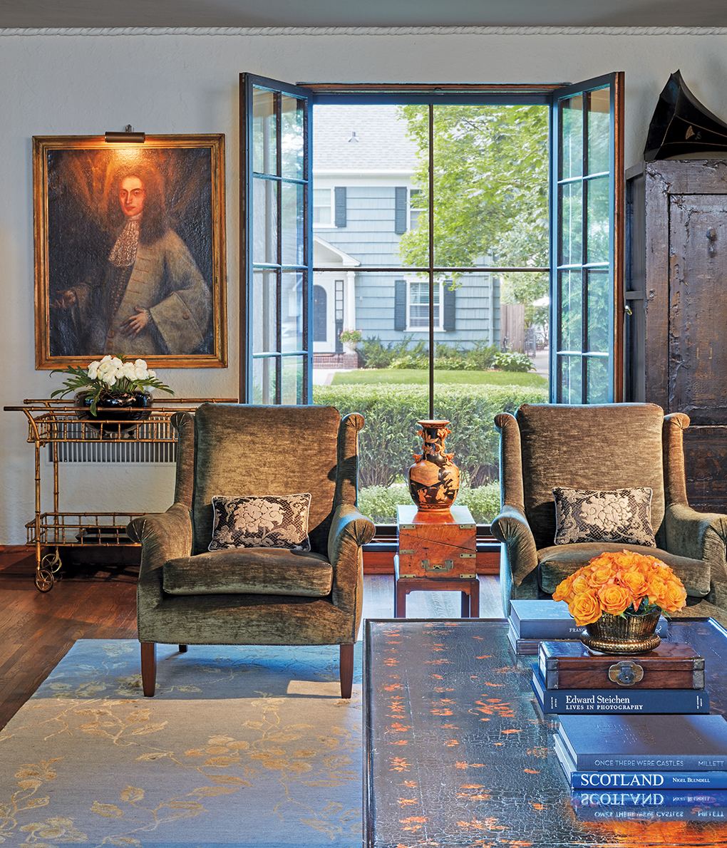 A living room featuring a pair of chairs, silk-wool rug, gold-painted bamboo bar cart, and painting.