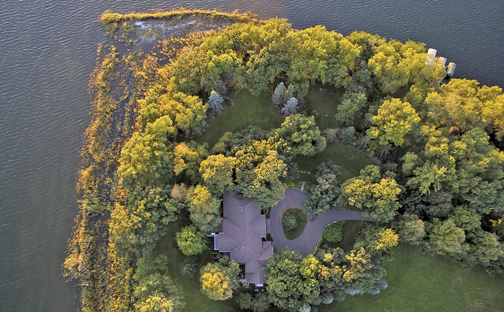 An aerial view of a lakeside home shows a home surrounded by trees and water.
