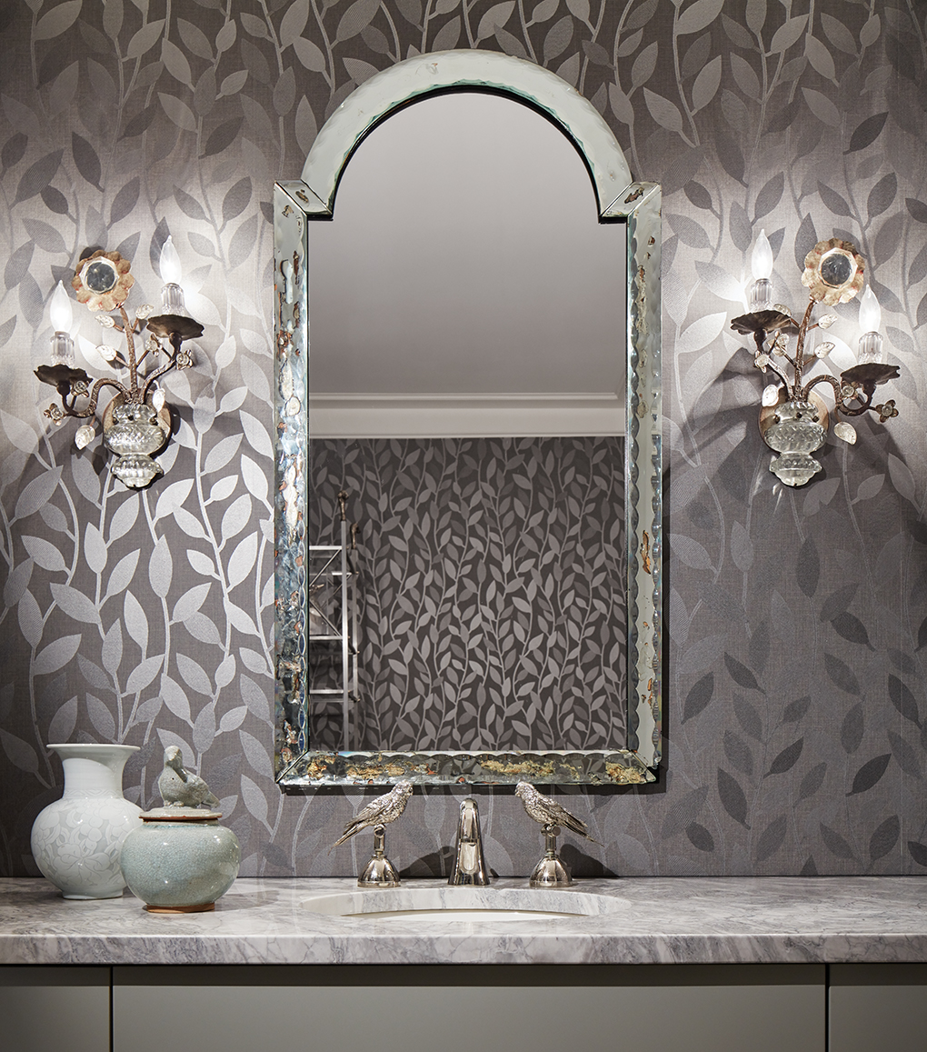 A remodeled guest bath featuring whimsical twin bird faucets, a mirror flanked by wall sconces and a gray metallic vine wallcovering.