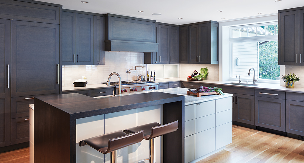 A renewed kitchen featuring dark cabinetry with horizontal wood grain panels and modern hardware. A two-part island accommodates prepping, seating and eating.