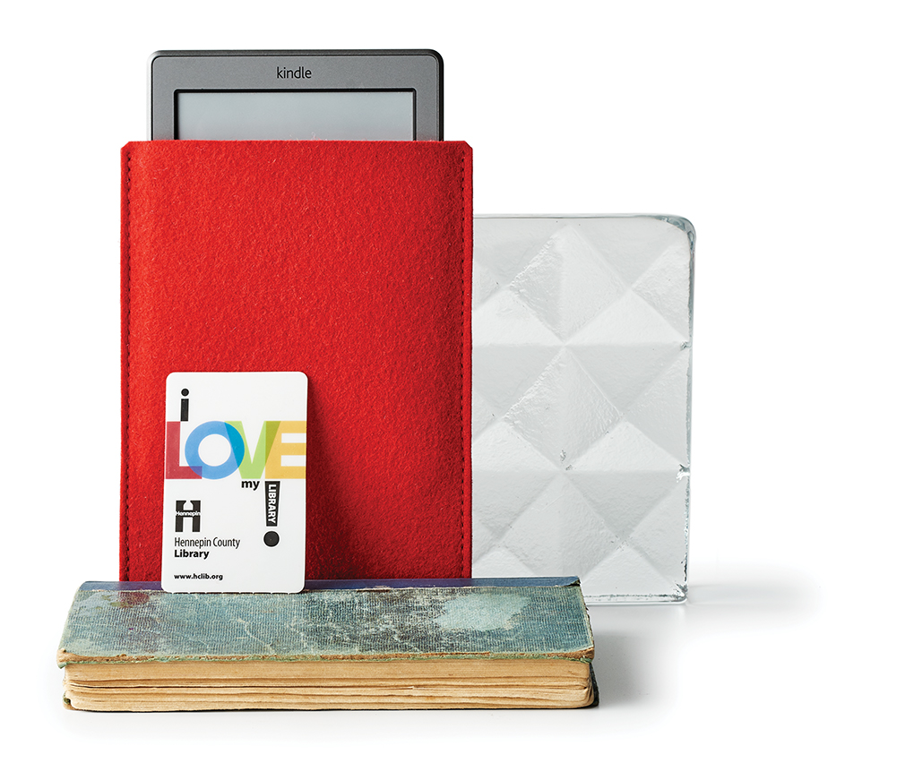 An Amazon kindle in a red cover along with a library card and books.