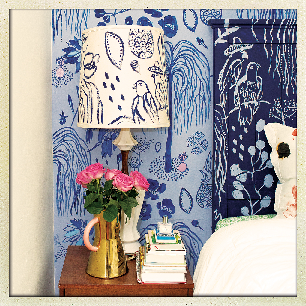 A lamp, books and potted plant sit on a nightstand next to a bed. The lamp shade and wallpaper feature designs by Kate Worum.