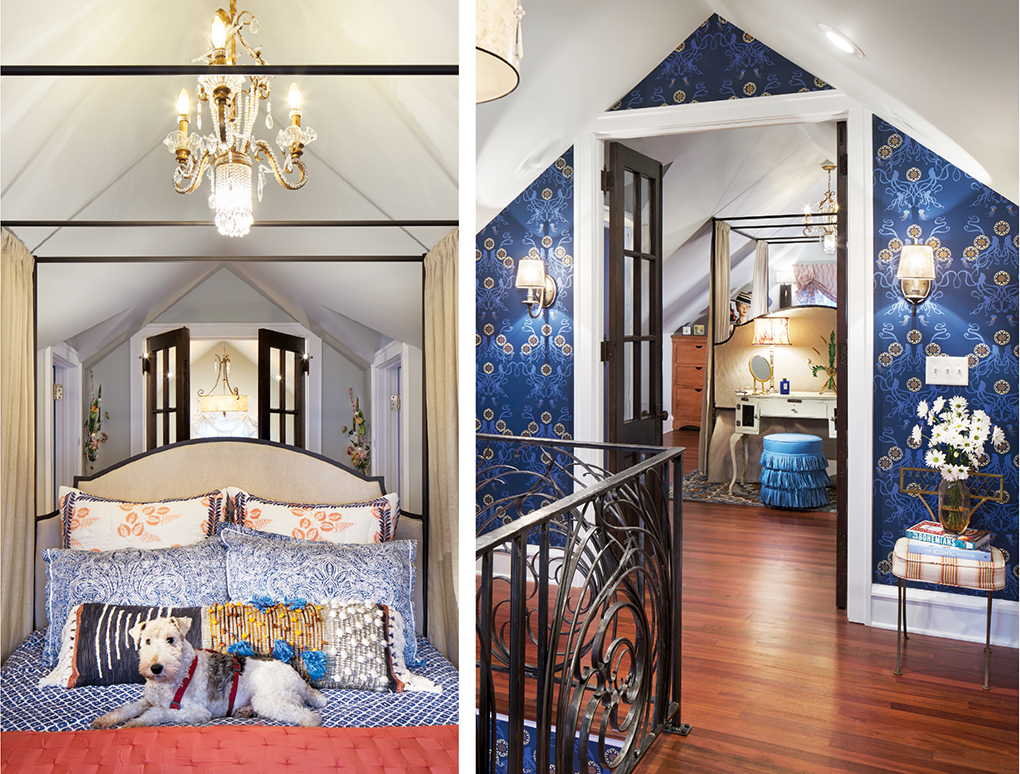 A master bedroom showing blue, patterned wallpaper, bedspread and pillows. A coral blanket and family dog rest on the bed underneath a chandelier.