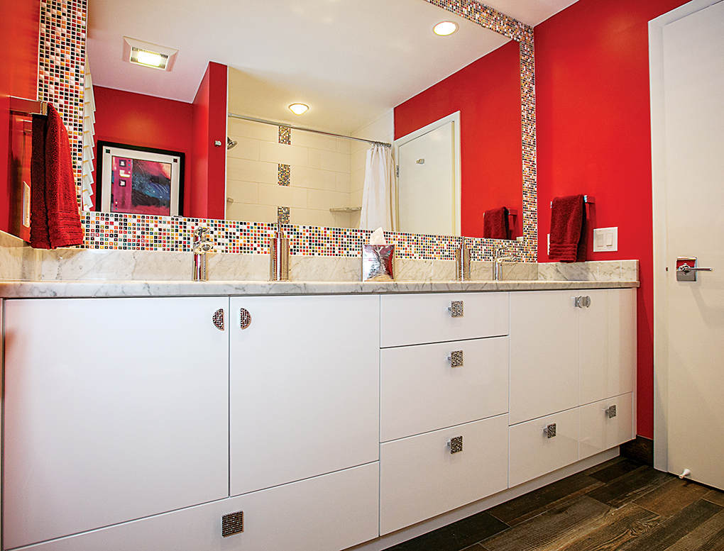 A bathroom featuring red walls, wood-plank floor tile, colorful mosaic tiles above the vanity and marble countertops.