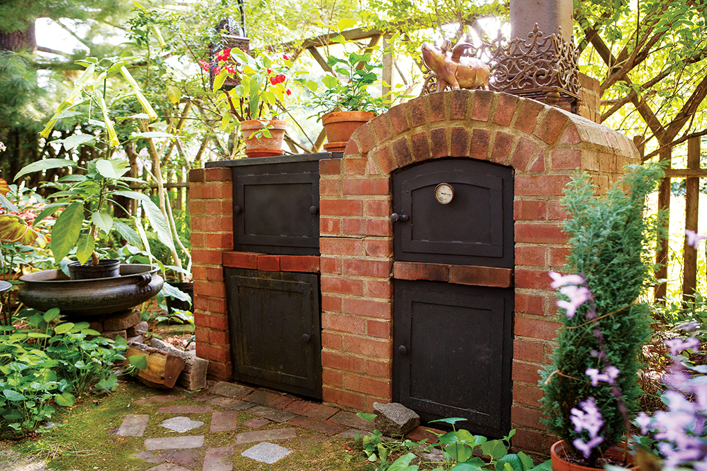 A brick oven and barbeque is flanked greenery.