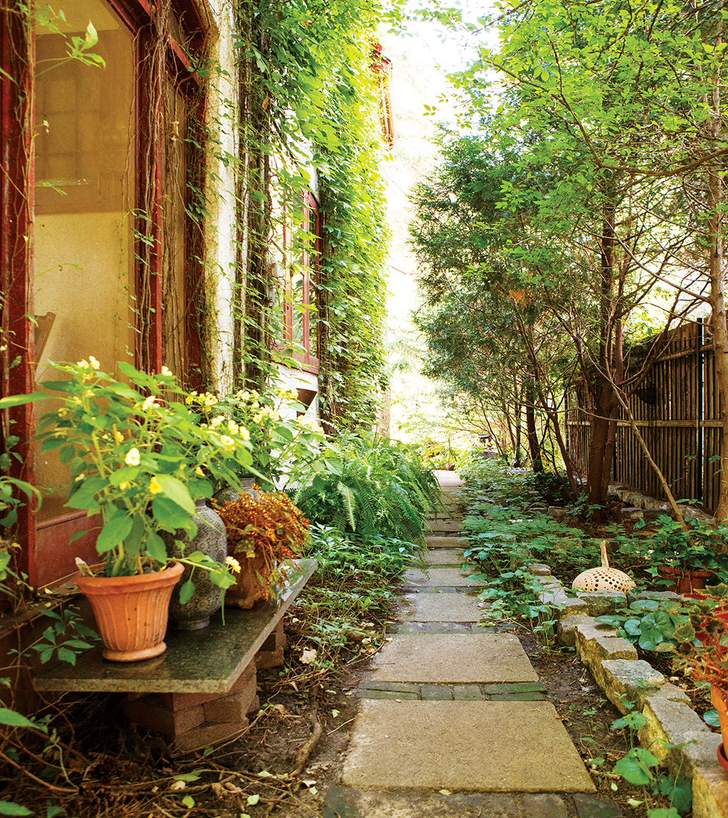 Pots and plants line a stone walkway leading to the back of a home.