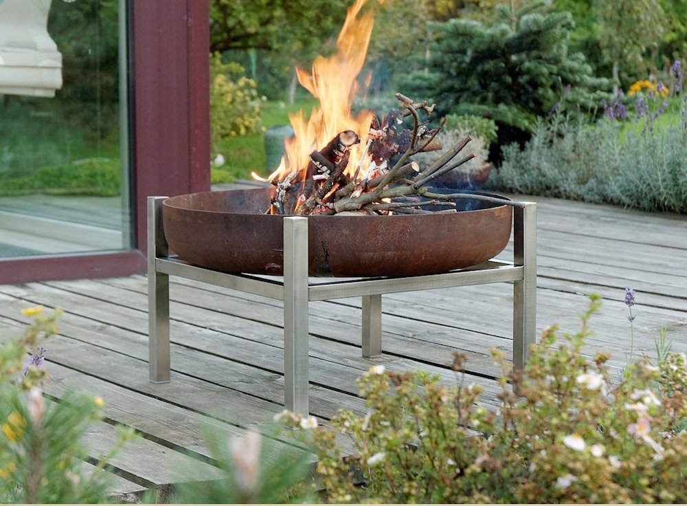 A fire pit with legs on a porch.