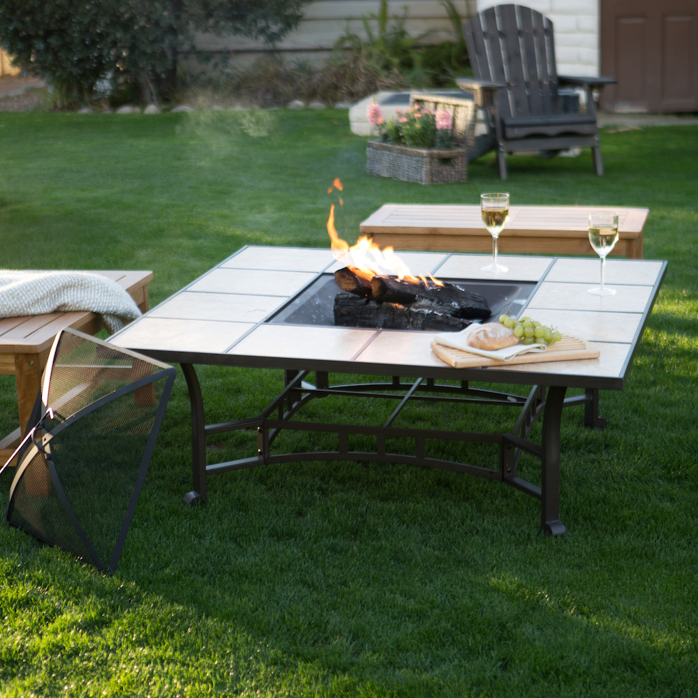A fire pit built into a table. On the table rest glasses of wine, and benches surround it.