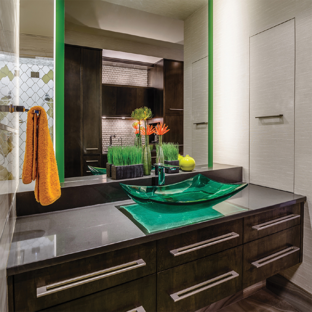 Modern looking bathroom with green glasses sink and dark counter space