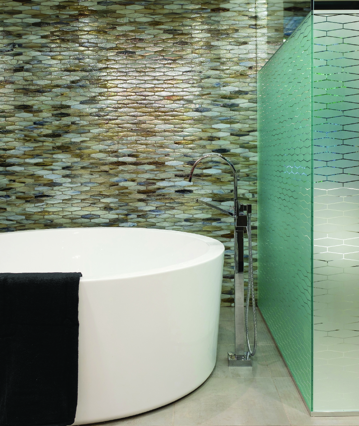 White bathtub with stone walls and glass shower