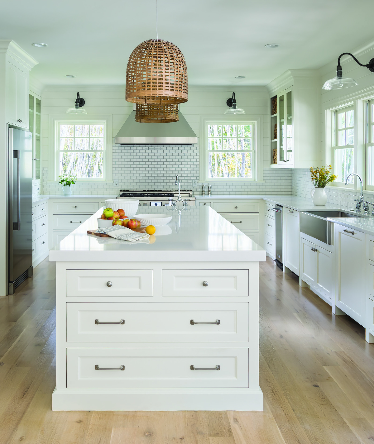 An all-white kitchen with stainless steel appliances, subway tile backsplash, and center island, a winner of the National Kitchen and Bath Association Minnesota Design Awards.