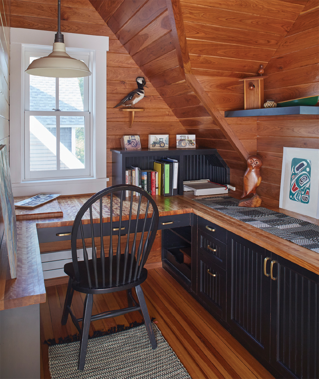 Wood nook with black chair and black bottom cabinets and white windows