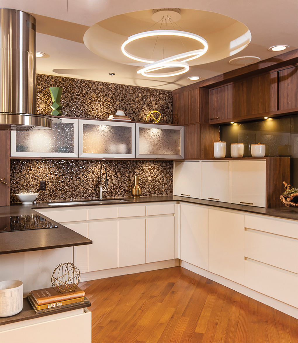 Showroom with mosaic backsplash, stainless steel vent, twisty light and white cabinets