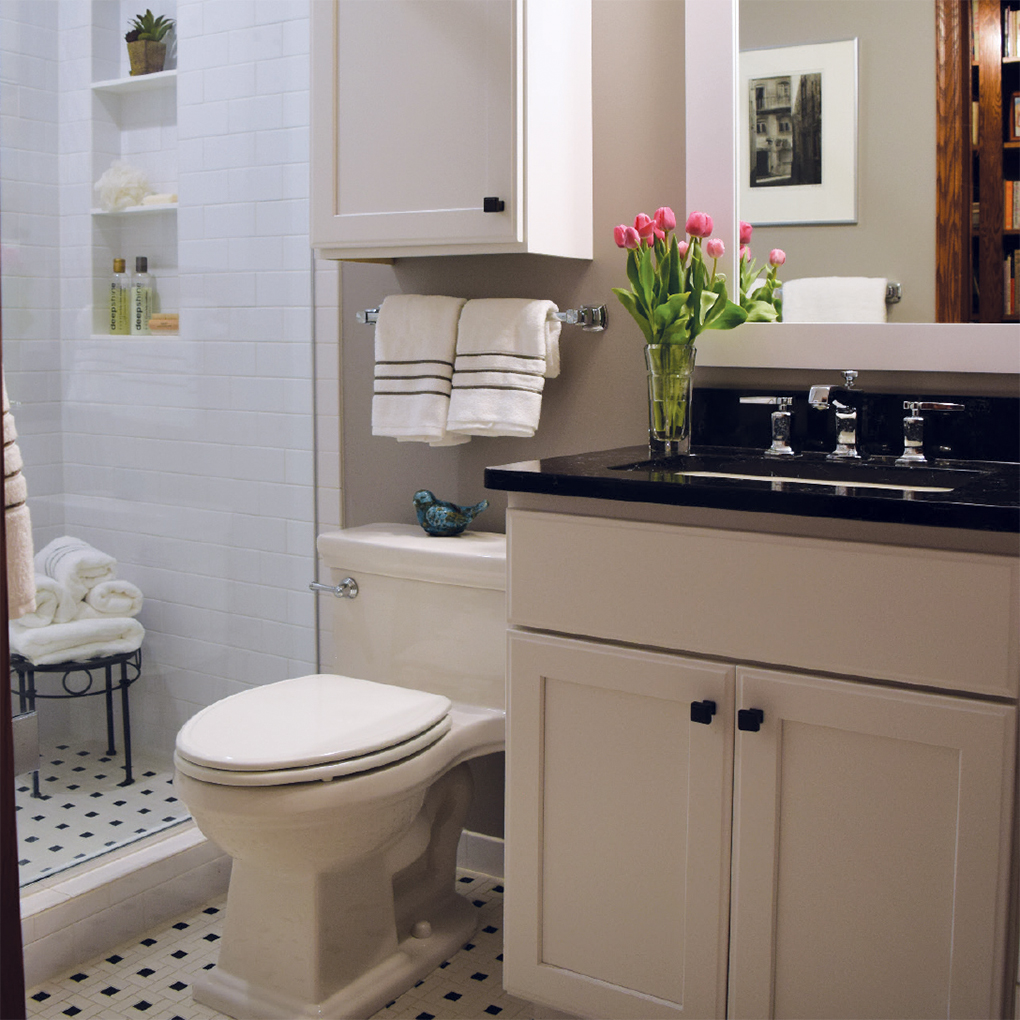 White bathroom with white toilet and black and white palette and pinwheel designs on tiles