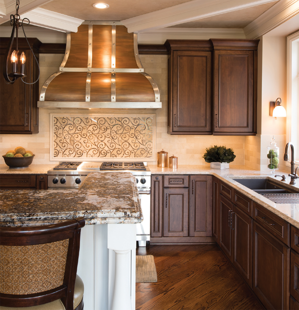 Kitchen with custom hood, caramel toned wood cabinetry and artful backsplash