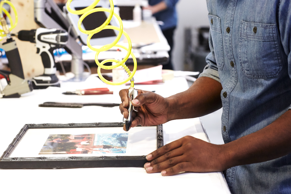 A person putting a frame on a picture at Framebridge.