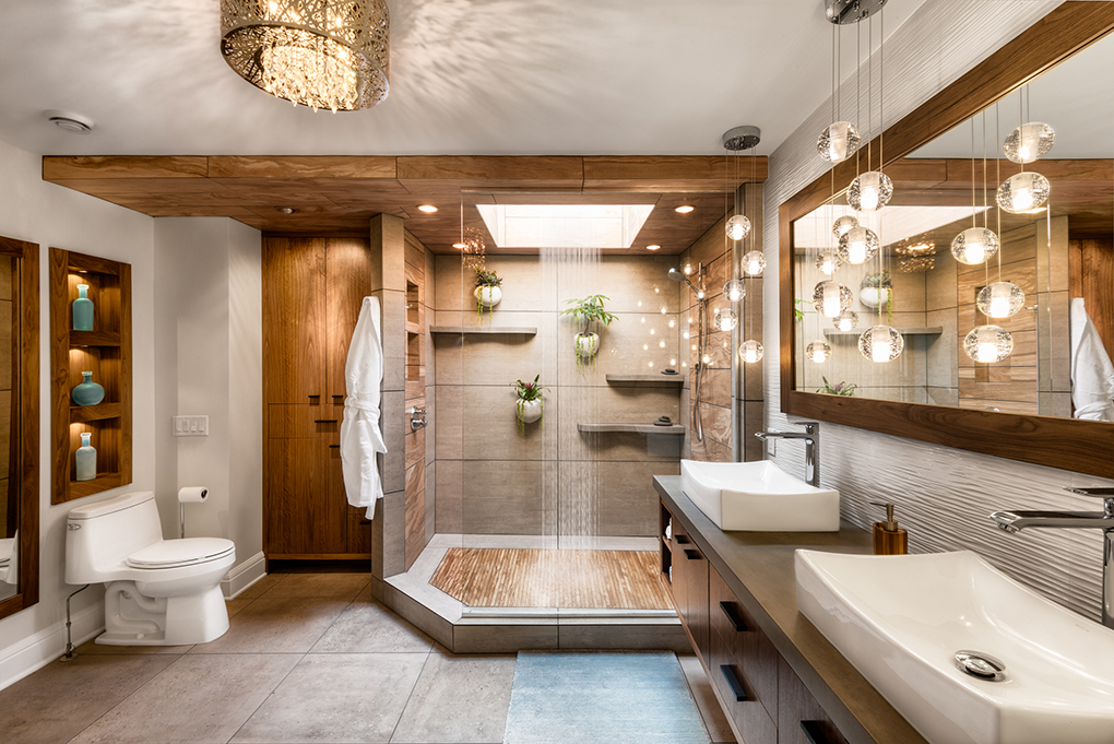 A large and elegant bathroom with two sinks, larg-tiled floor, wood cabinetry and large rain shower.