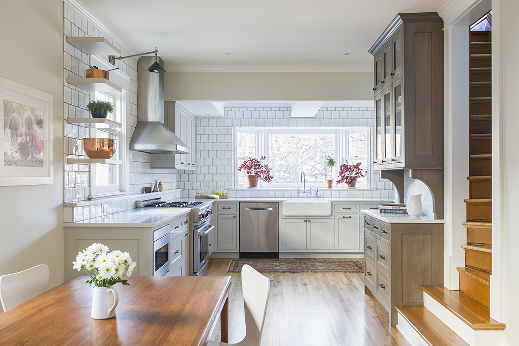 Pretty kitchen with gray cabinets and staircase coming down from second floor.