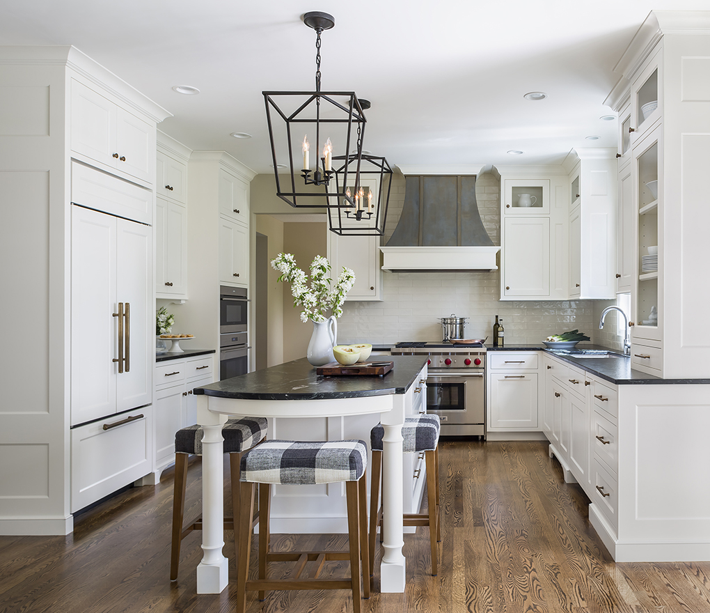 White kitchen with touches of black and hardwood flooring.