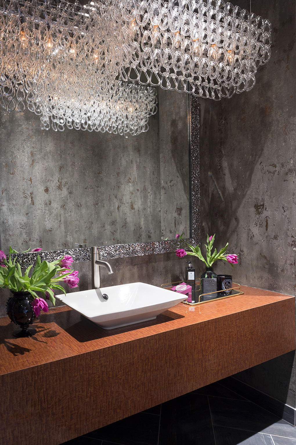 An elegant powder room with dark walls, large mirror, and white sink flanked by pink flowers in vases.
