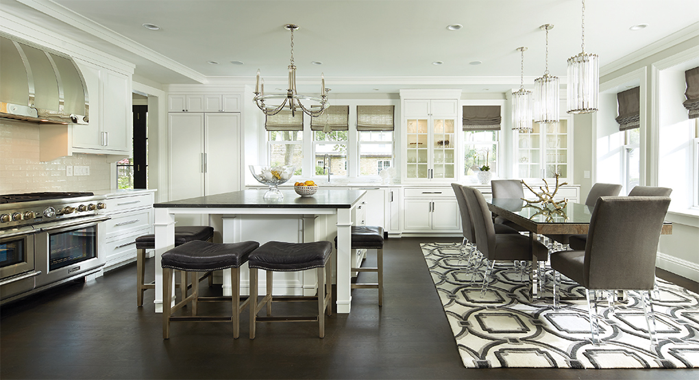 An expansive, all white kitchen and dining room with center island.