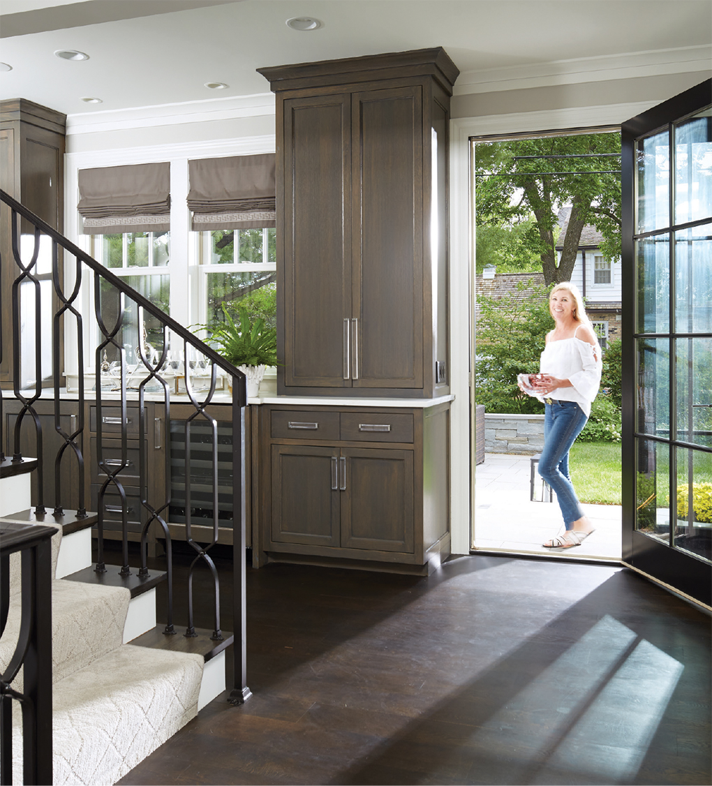 Kathy Nelsen stands outside on her back patio with the door open to reveal the wet bar in her home's basement.