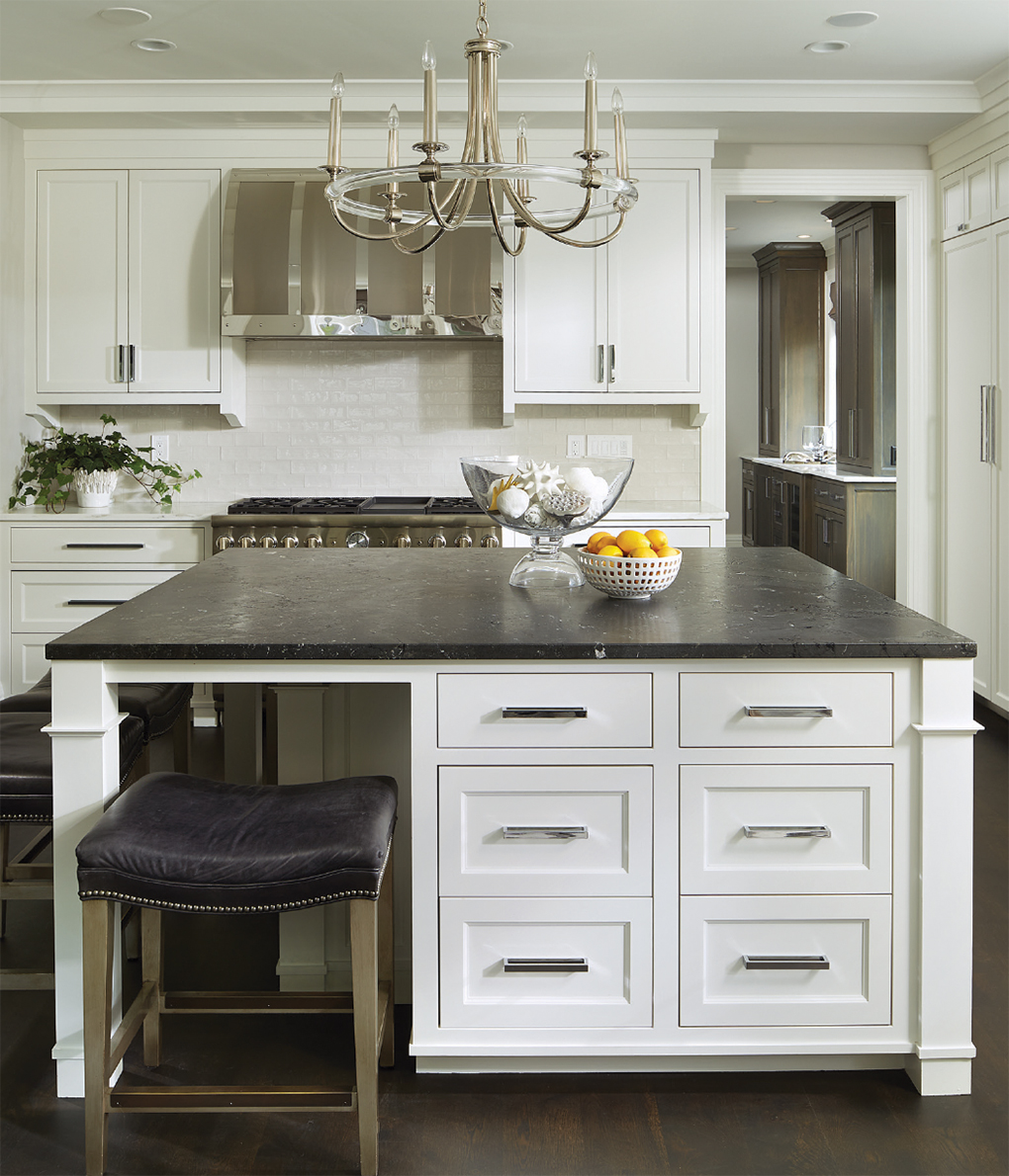 A kitchen island with a black quartzite top in an all white kitchen.